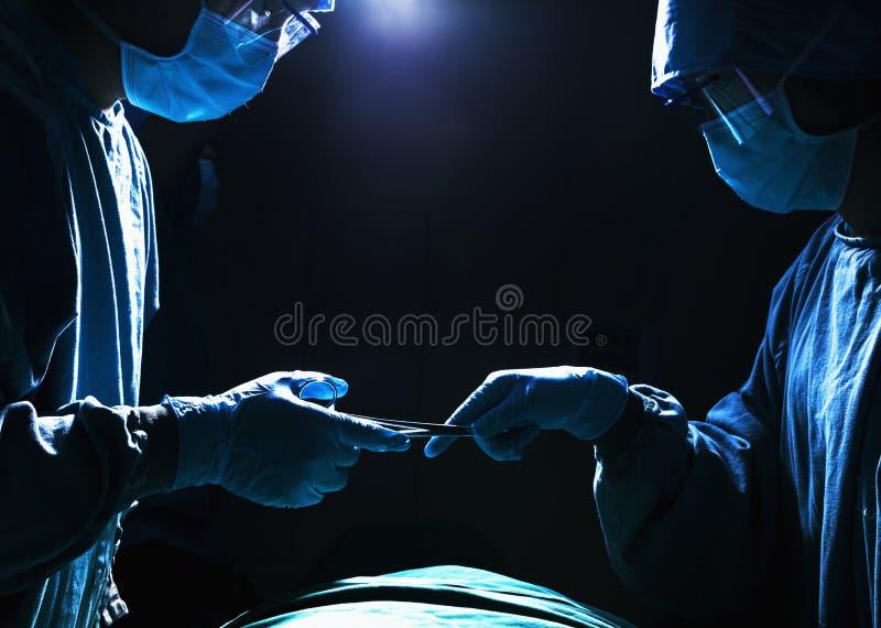 Dos cirujanos que trabajan y que pasan el equipo quirúrgico en la sala de operaciones, oscura fotos de archivo libres de regalías