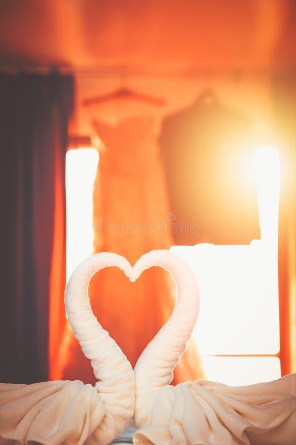 Dos cisnes hechos de toallas en el cuarto con la camisa del novio y el vestido de la novia que cuelgan detrás foto de archivo libre de regalías