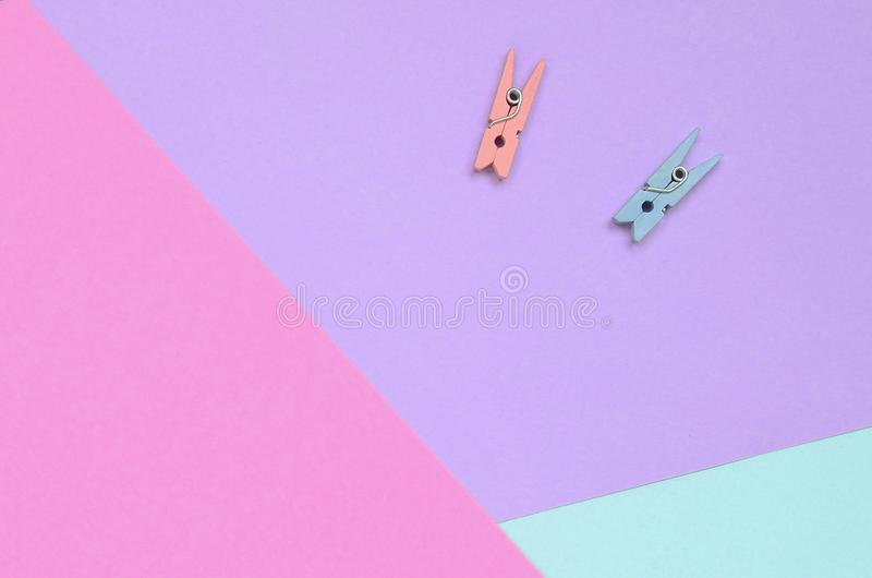 Dos clavijas de madera coloreadas mienten en el fondo de la textura del papel en colores pastel de la violeta de la moda, azul y  imagenes de archivo