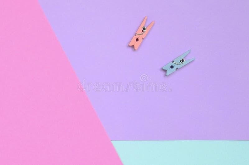 Dos clavijas de madera coloreadas mienten en el fondo de la textura del papel en colores pastel de la violeta de la moda, azul y  fotos de archivo libres de regalías