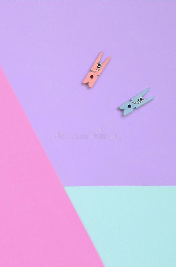 Dos clavijas de madera coloreadas mienten en el fondo de la textura del papel en colores pastel de la violeta de la moda, azul y  fotografía de archivo