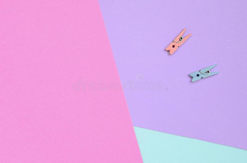 Dos clavijas de madera coloreadas mienten en el fondo de la textura del papel en colores pastel de la violeta de la moda, azul y  imágenes de archivo libres de regalías