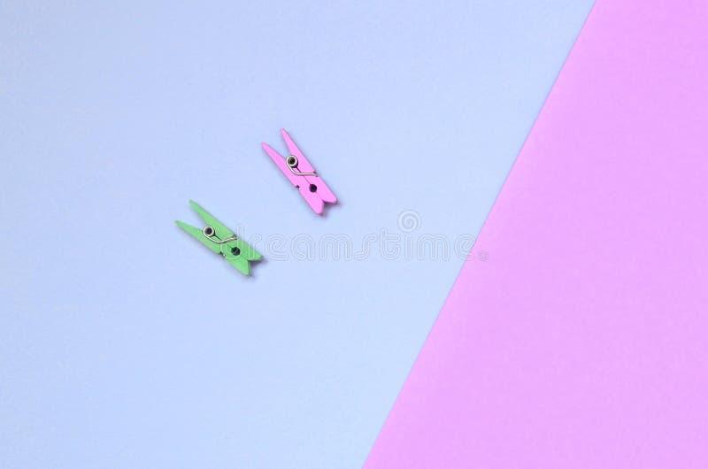 Dos clavijas de madera coloreadas mienten en el fondo de la textura del papel violeta de la moda y rosado en colores pastel de lo fotografía de archivo