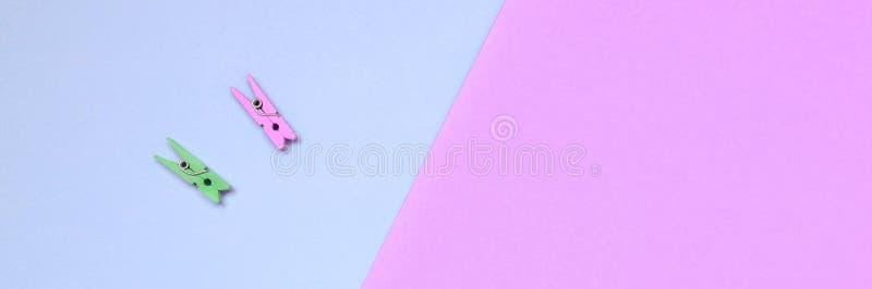 Dos clavijas de madera coloreadas mienten en el fondo de la textura del papel violeta de la moda y rosado en colores pastel de lo imagenes de archivo