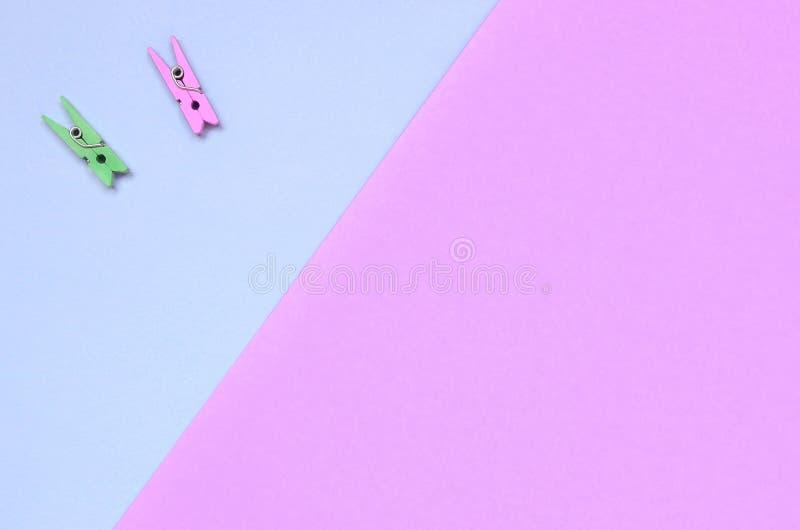 Dos clavijas de madera coloreadas mienten en el fondo de la textura del papel violeta de la moda y rosado en colores pastel de lo imagen de archivo