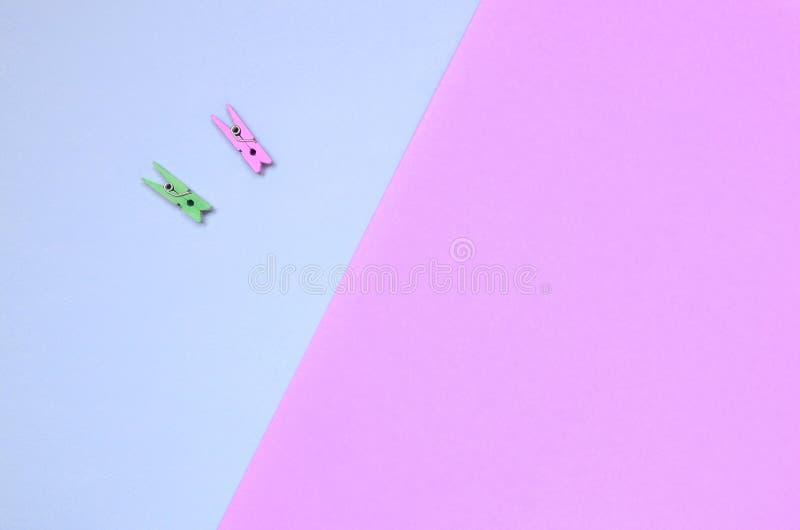 Dos clavijas de madera coloreadas mienten en el fondo de la textura del papel violeta de la moda y rosado en colores pastel de lo foto de archivo libre de regalías