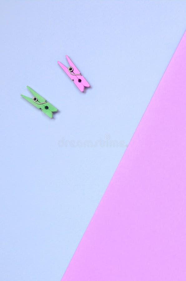 Dos clavijas de madera coloreadas mienten en el fondo de la textura del papel violeta de la moda y rosado en colores pastel de lo fotos de archivo libres de regalías