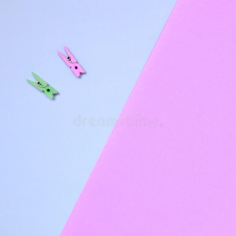 Dos clavijas de madera coloreadas mienten en el fondo de la textura del papel violeta de la moda y rosado en colores pastel de lo fotos de archivo