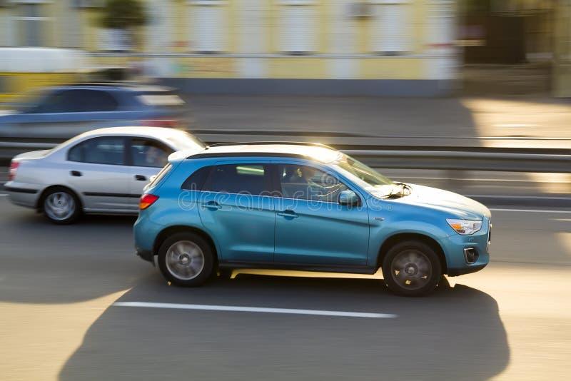 Dos coches azul y gris que se mueven rápidamente a lo largo del camino de ciudad limpio en día soleado brillante Fondo borroso de fotografía de archivo libre de regalías