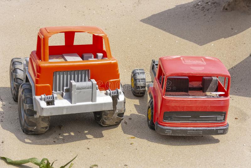 Dos coches del juguete de los niños, soporte seminuevo, quebrado en la arena debajo del sol brillante del verano fotos de archivo libres de regalías