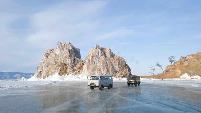 Dos coches viejos de la excursi?n en el fondo de la roca de Shamanka cerca de la isla de Olkhon Los coches est?n en el hielo del  foto de archivo