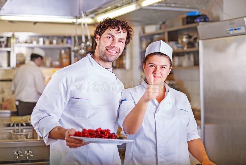 Dos cocineros cocinan juntos Concepto del proceso de cocinar fotos de archivo