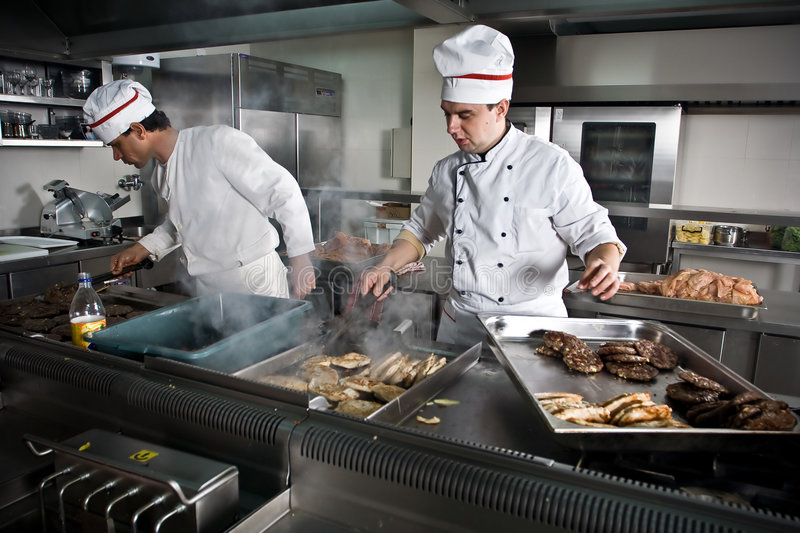 Dos cocineros en el trabajo imagenes de archivo