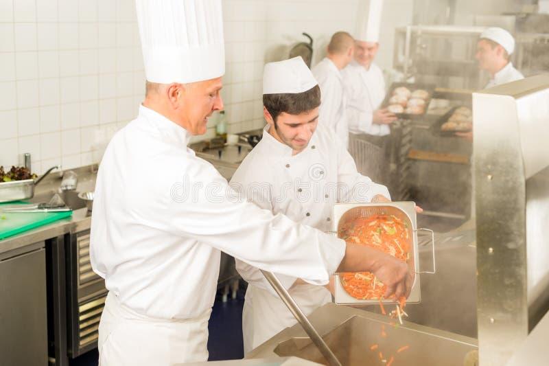 Dos cocineros profesionales que cocinan en cocina fotos de archivo