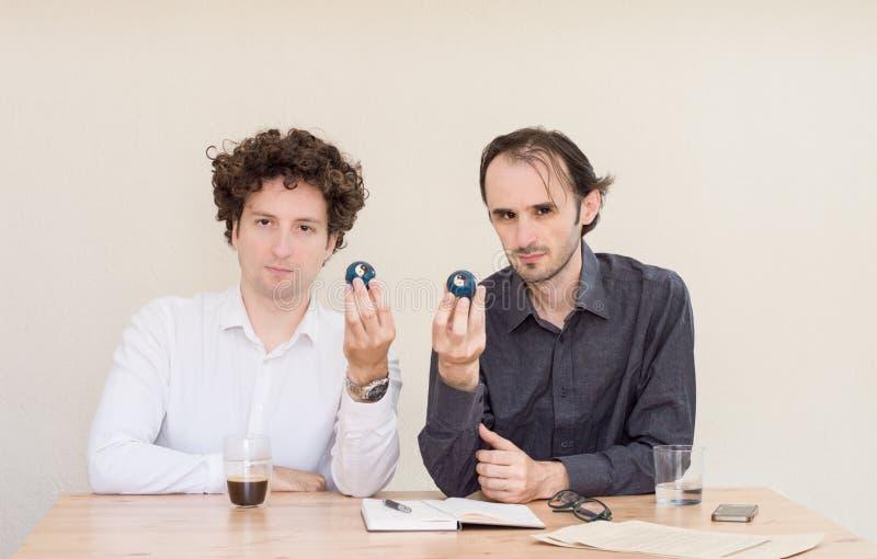 Dos colegas caucásicos jovenes que se sientan en la tabla, sosteniendo las bolas de Yin Yang del chino en la oficina con el fondo fotografía de archivo