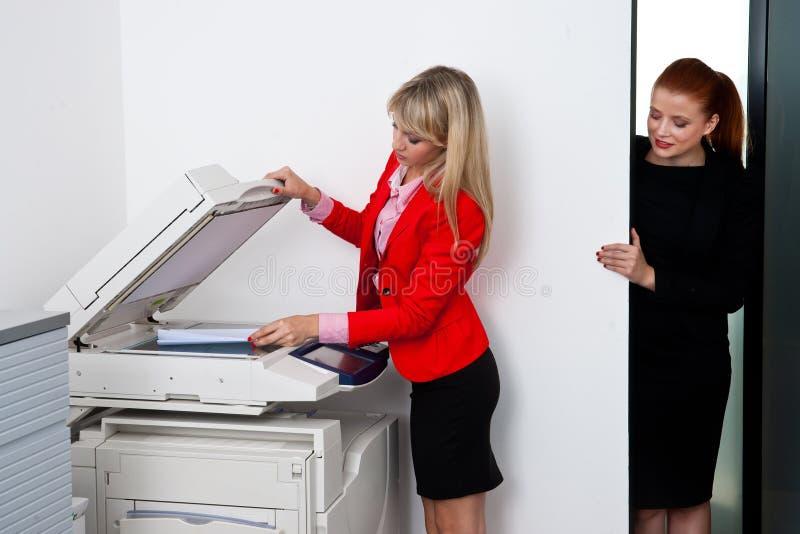 Dos colegas de la mujer que trabajan en la impresora en oficina fotografía de archivo libre de regalías