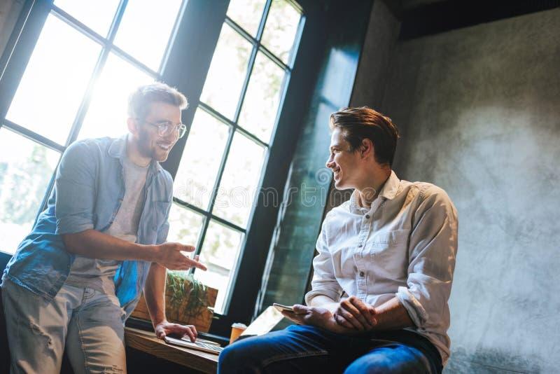 Dos colegas del negocio que se sientan en una tabla, teniendo una reunión fotografía de archivo