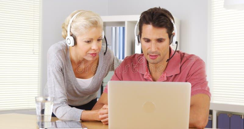 Dos colegas del negocio que tienen una videoconferencia en el ordenador portátil fotos de archivo libres de regalías