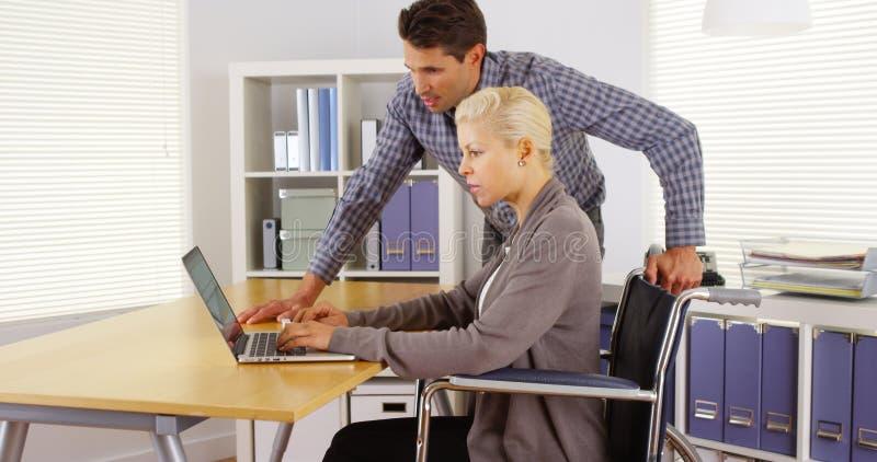 Dos colegas del negocio que trabajan en el escritorio foto de archivo