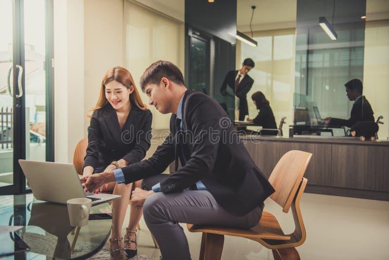 Dos colegas del negocio que trabajan en su oficina usando una mesa fotos de archivo