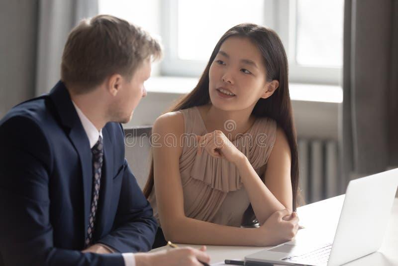 Dos colegas diversos que hablan para sentarse en el escritorio de oficina con el ordenador portátil fotografía de archivo