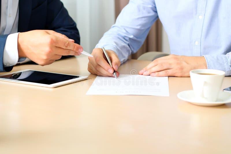 Dos colegas están firmando un contrato, reunión de negocios en la oficina imagen de archivo libre de regalías