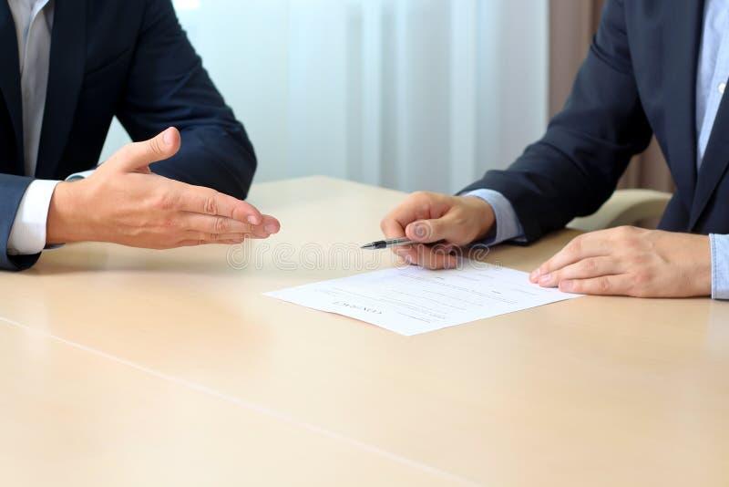 Dos colegas están firmando un contrato, reunión de negocios en la oficina imagenes de archivo