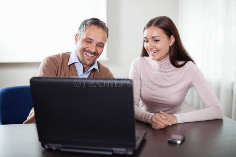 Dos colegas felices del asunto que trabajan en la computadora portátil imágenes de archivo libres de regalías