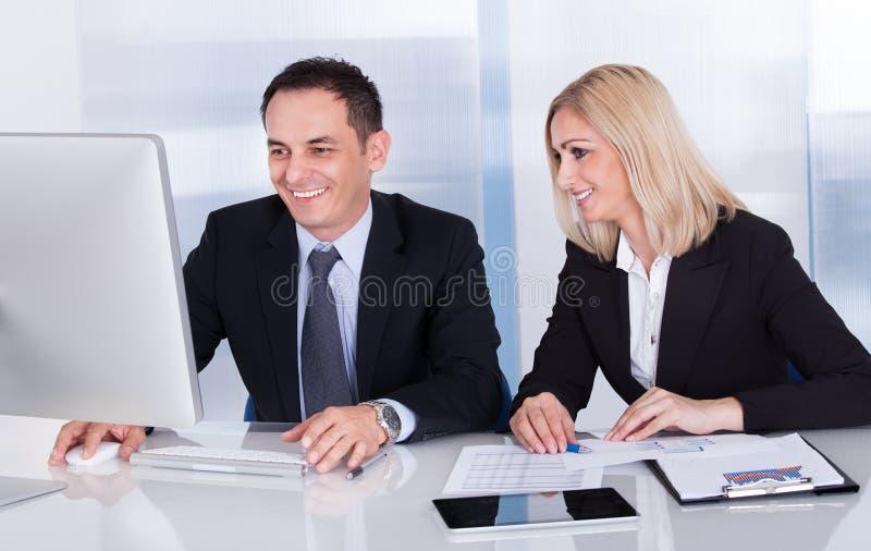 Dos colegas felices del negocio en la oficina fotos de archivo