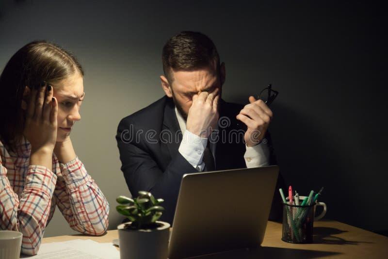 Dos colegas que se encuentran en oficina oscura de la tarde para solucionar un problema fotos de archivo libres de regalías
