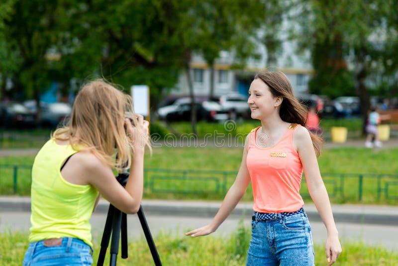 Dos colegialas de las muchachas, en el verano en la ciudad Escribe el vídeo a la cámara Sonrisa feliz Vlog y blog de registro foto de archivo libre de regalías