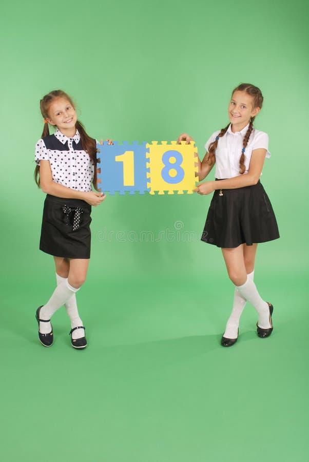 Dos colegialas llevan a cabo al tablero del color con el número dieciocho fotografía de archivo