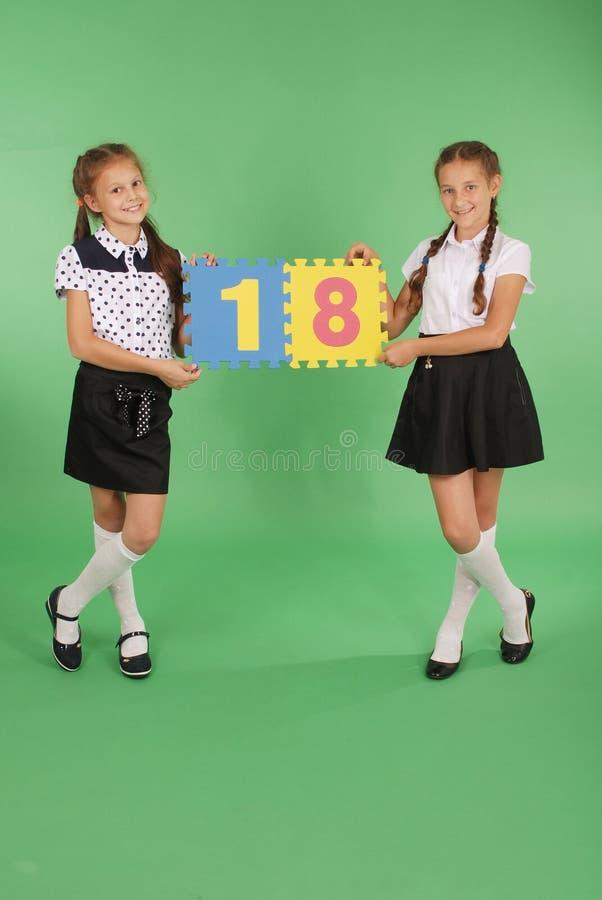 Dos colegialas llevan a cabo al tablero del color con el número dieciocho imagenes de archivo