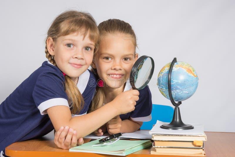 Dos colegialas que miran el globo a través de una lupa fotos de archivo libres de regalías