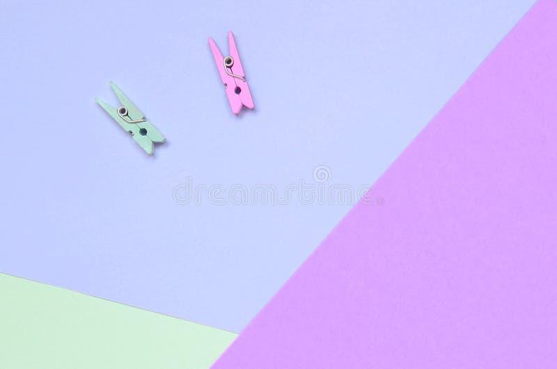 Dos colorearon clavijas de madera mienten en el fondo de la textura de la violeta en colores pastel de la moda, de la turquesa y  imágenes de archivo libres de regalías
