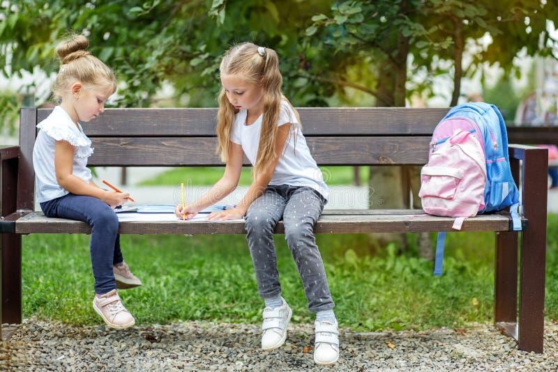 Dos compañeros de clase de los niños dibujan en el parque de la escuela El concepto de escuela, amistad, dibujo, estudio, afición fotos de archivo libres de regalías