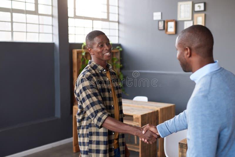 Dos compañeros de trabajo africanos sonrientes que sacuden las manos juntas en una oficina imagenes de archivo
