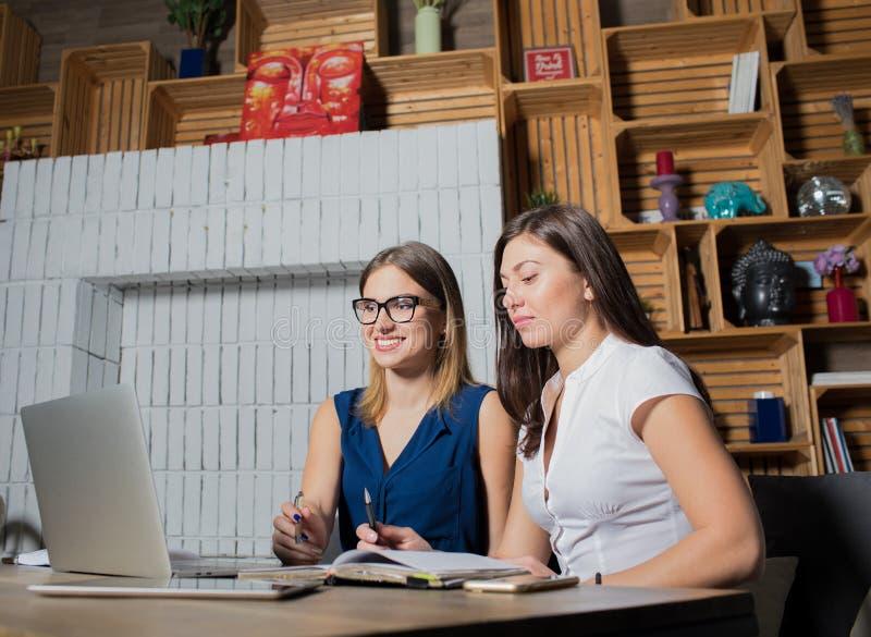 Dos compañeros de trabajo jovenes que tienen llamada video en línea en el ordenador portátil, sentándose en interior moderno de l imagen de archivo