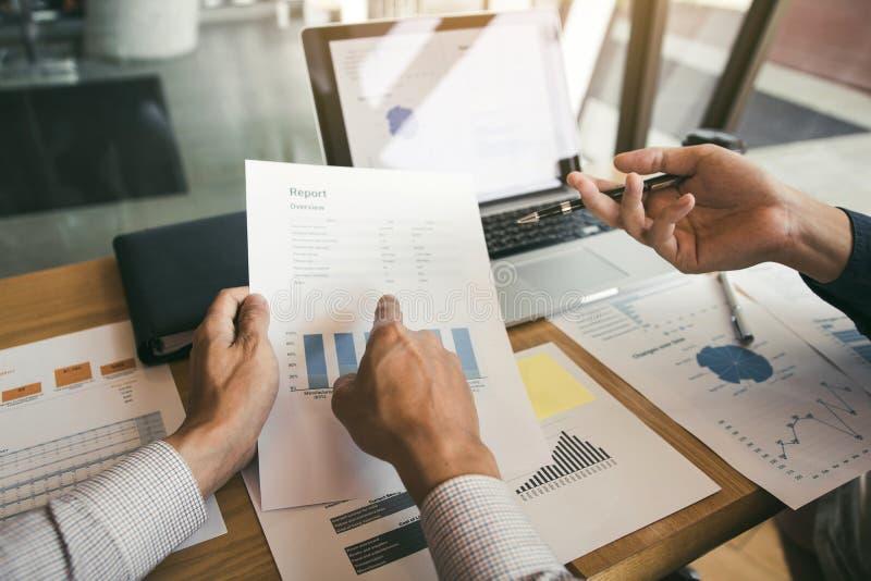 Dos compañeros de trabajo de la sociedad del negocio y el gesticular con la discusión de un gráfico y de una compañía de la plani imagen de archivo libre de regalías