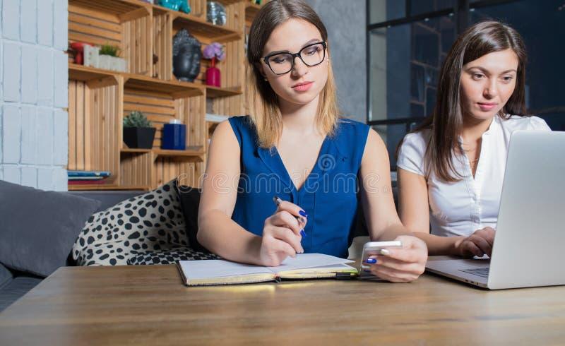 Dos compañeros de trabajo de las mujeres que tienen trabajo común con el teléfono del red-libro y de célula imagen de archivo