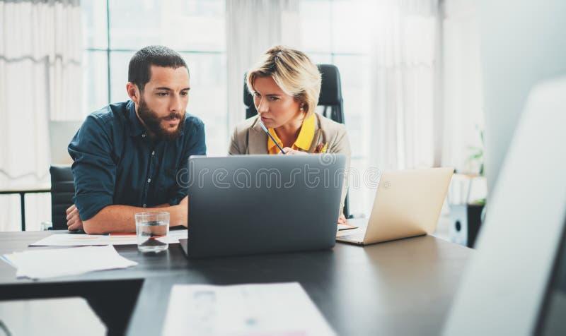 Dos compa?eros de trabajo en el proceso de trabajo Mujer joven que trabaja as? como colega en la oficina moderna Concepto del tra foto de archivo