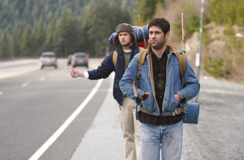 Dos compinches que acampan que hacen autostop imagen de archivo libre de regalías