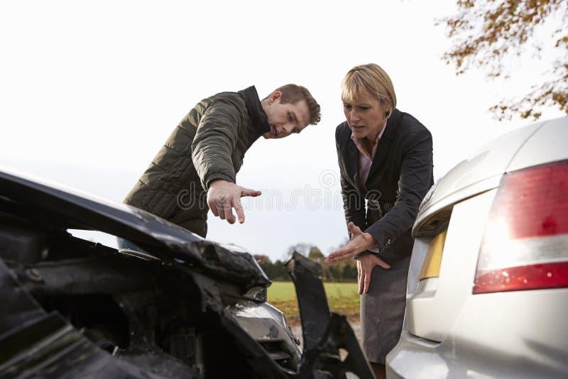 Dos conductores que discuten sobre daño a los coches después de accidente foto de archivo