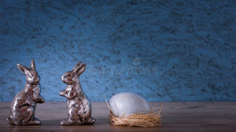 Dos conejos con un huevo en la jerarquía fotos de archivo libres de regalías