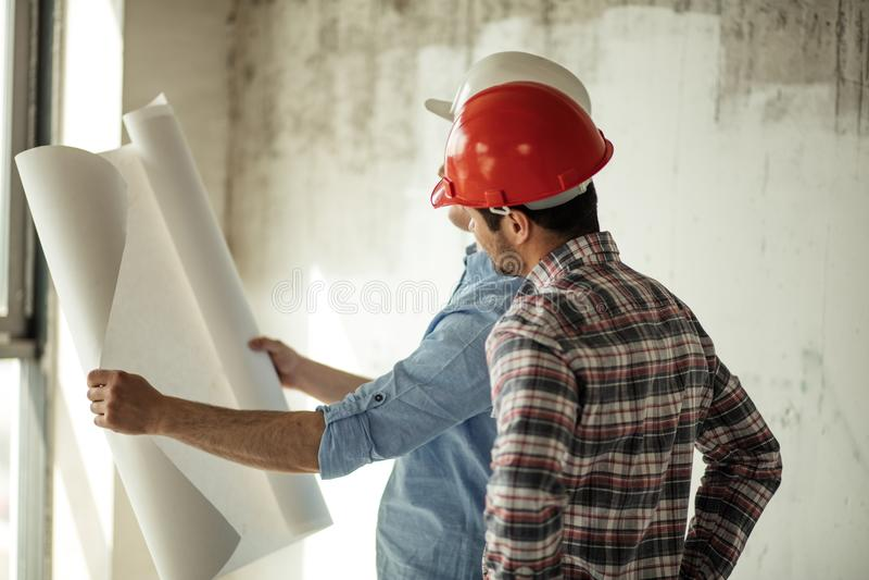 Dos constructores cooperativos están mirando el bluerprint de una nueva alameda de compras fotografía de archivo libre de regalías