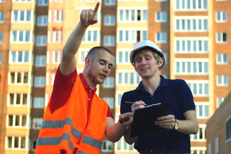 Dos constructores del ingeniero con el modelo planean en el emplazamiento de la obra fotografía de archivo