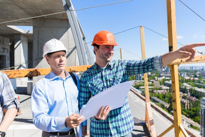 Dos constructores en el emplazamiento de la obra que mira la reunión del contratista de los planes con el hombre de negocios imagenes de archivo