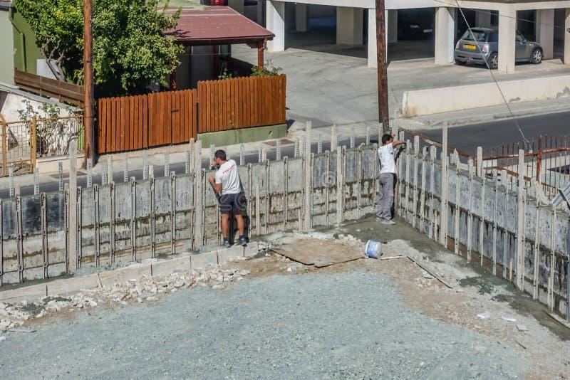 Dos constructores que trabajan en un muro de cemento nuevamente construido Quitando shuttering que ha apoyado la estructura foto de archivo libre de regalías