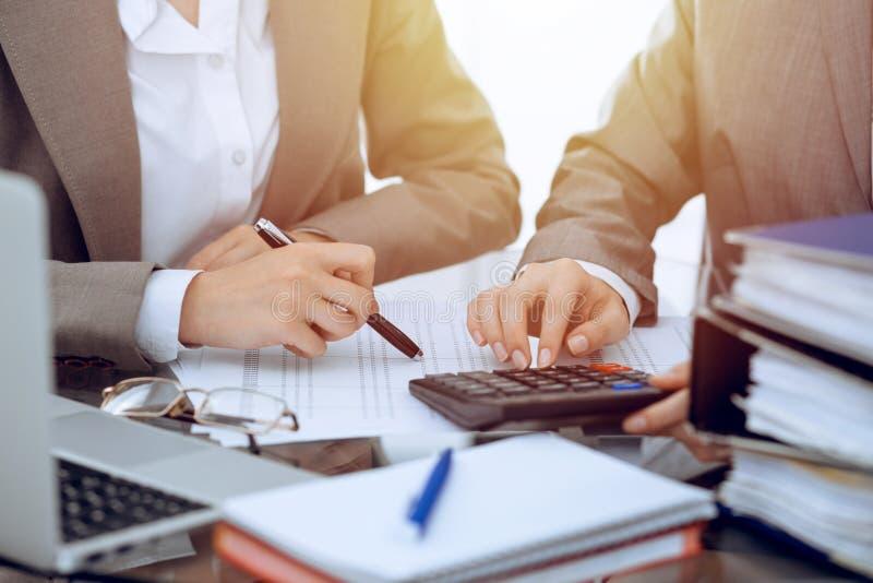 Dos contables de sexo femenino que cuentan en la renta de la calculadora para el primer de las manos de la realizaci?n de la form fotografía de archivo libre de regalías
