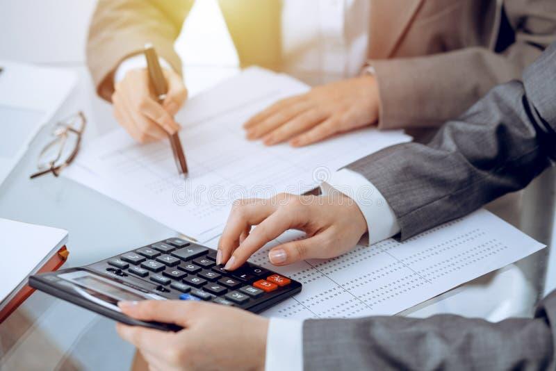 Dos contables de sexo femenino que cuentan en la renta de la calculadora para el primer de las manos de la realizaci?n de la form imagen de archivo libre de regalías